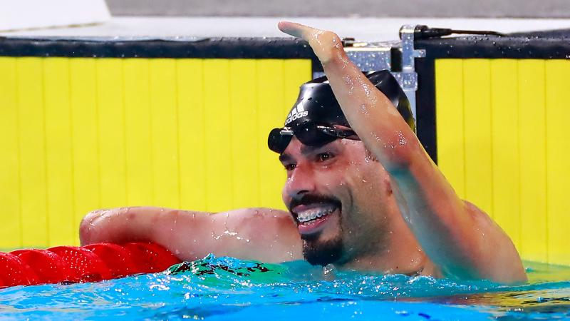 a male Para swimmer raises his arm in celebration in the pool