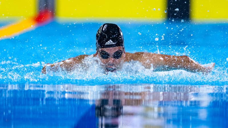 a male Para swimmer doing a butterfly stroke in the pool
