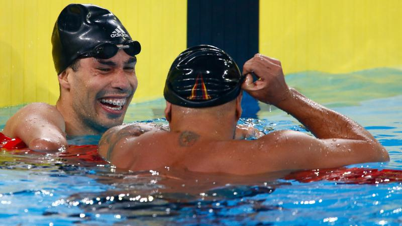 two male Para swimmers laughing in the water