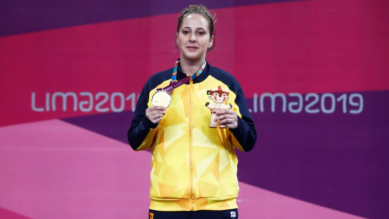 a female Para judoka stands on the podium holding her gold medal