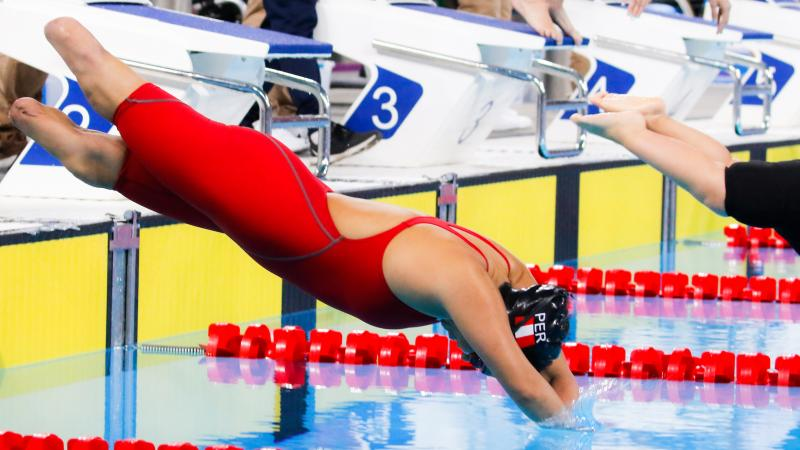 a female Para swimmer with no legs dives into the pool