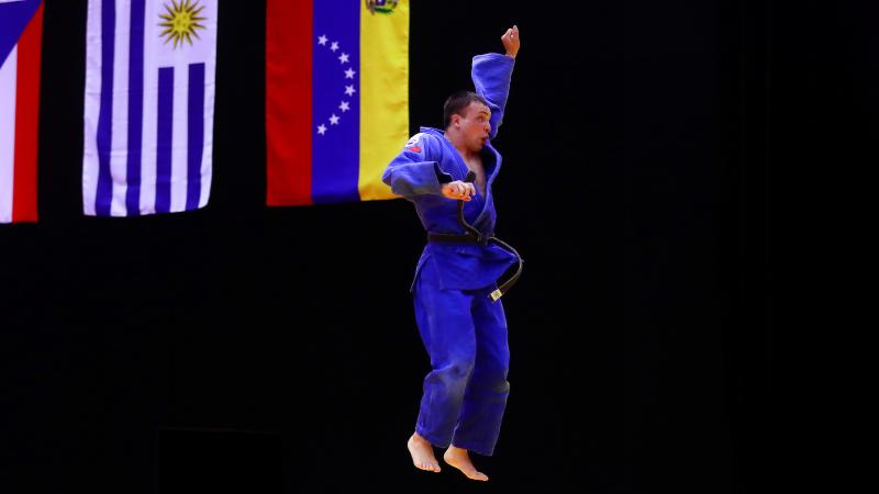 a male judoka jumps in the air in celebration