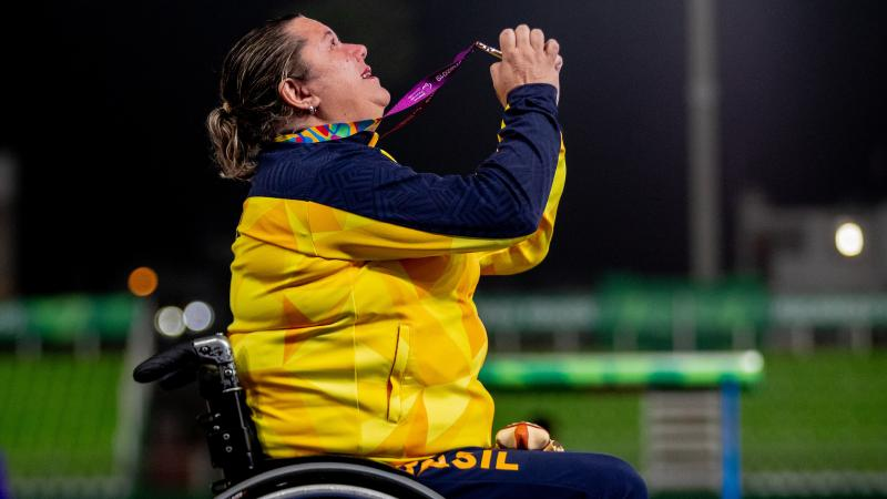 a female wheelchair athlete holds up her gold medal to the sky