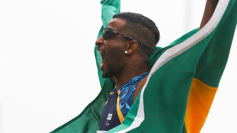 a male Para athlete cheers and holds up the Brazil flag