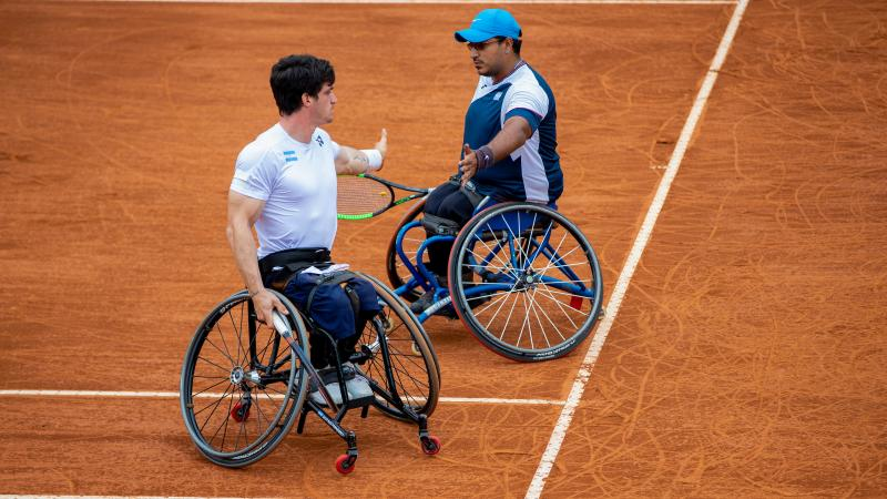 two male wheelchair tennis players high five on court