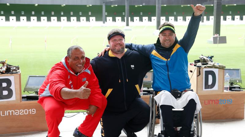 three male Para shooters with their arms around each other smiling