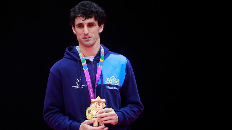 a male judoka stands on the podium with his gold medal
