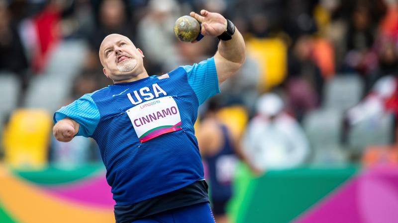 a male Para athlete throws a shot put