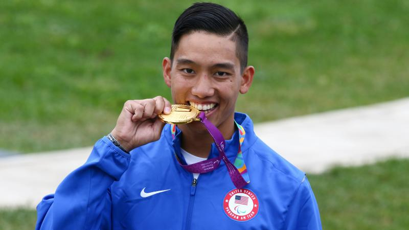 a male Para shooter biting a gold medal and smiling