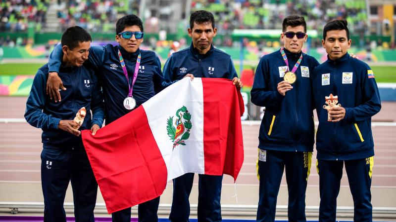 a group of vision impaired runners on the podium holding a Peru flag