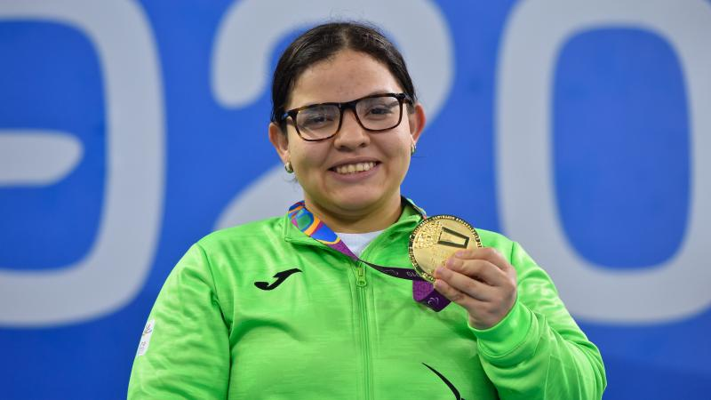 a female Para swimmer holding up her gold medal