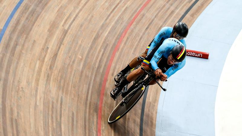 a male Para cycling tandem goes round a corner on the track