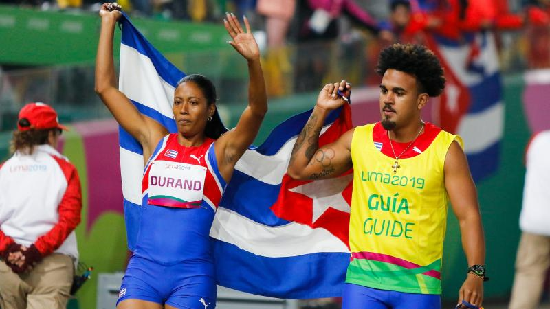 a female vision impaired runner and her male guide hold up the Cuba flag and wave