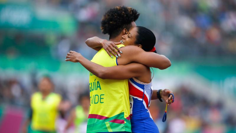 a female vision impaired runner hugs her guide