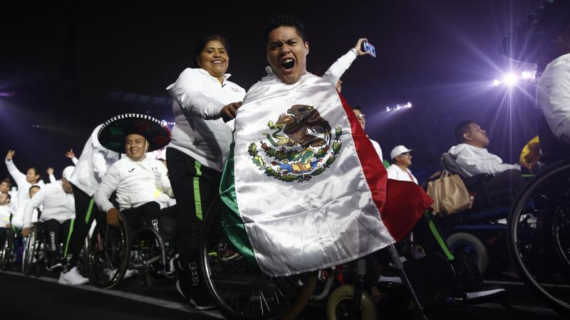 a male wheelchair athlete holds up a Mexican flag and cheers