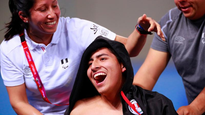 a male Para swimmer smiles as his assistants put his jacket on