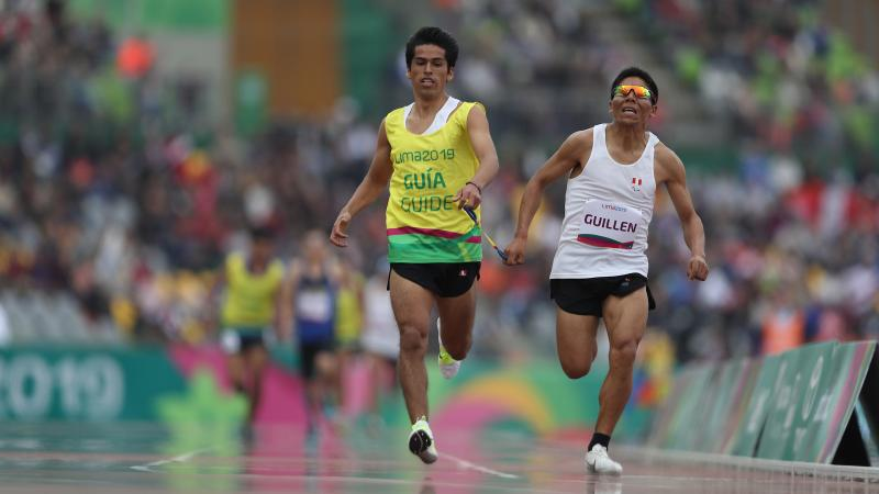 a male vision impaired runner and his guide sprinting to the finish line