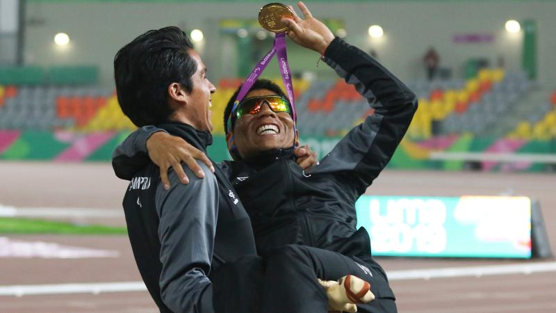 a male vision impaired runner being carried by his guide while waving his medal