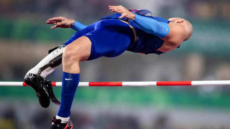 a male Para athlete with a prosthetic leg jumps backwards over a high bar