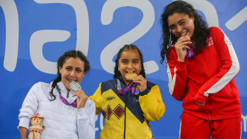 three female Para swimmers on the podium biting their medals