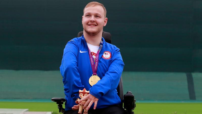 a male Para shooter in a wheelchair on the podium with a gold medal