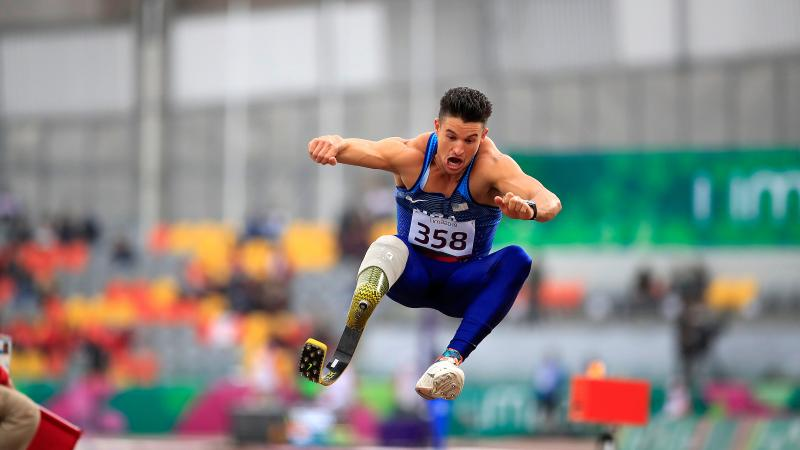 a male Para athlete with a prosthetic leg jumping into a sandpit