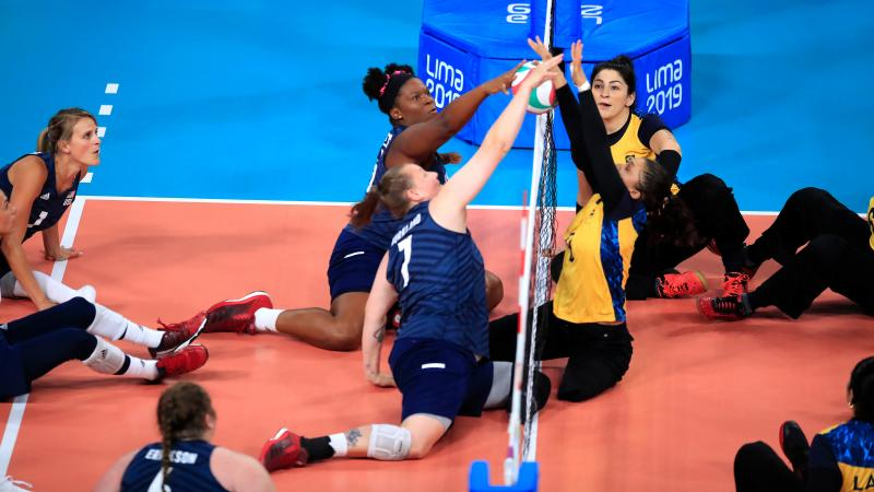 female sitting volleyball players contesting the ball over the net