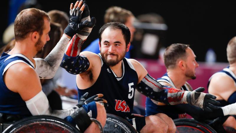 male wheelchair rugby players high-five