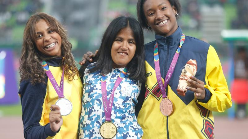 three female Para athletes with their medals on the podium