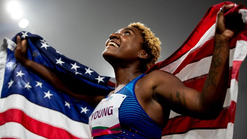 a female Para athlete holds up the United States flag