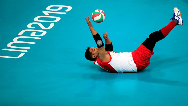 a male sitting volleyball player falls backwards to reach a ball