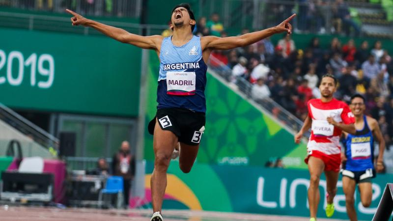 a male Para athlete celebrates with his arms wide