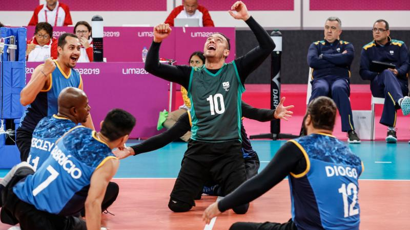 male sitting volleyball players celebrate on the court