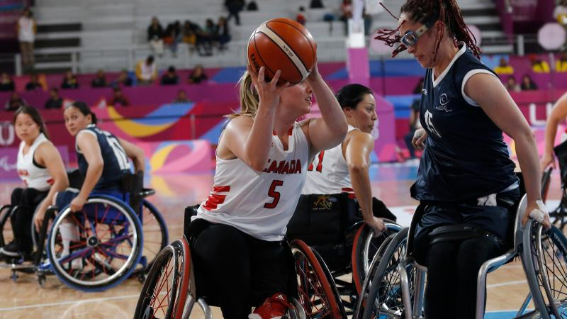 female wheelchair basketball players fight for the ball
