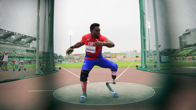 a male Para athlete with a prosthetic leg prepares to throw a discus