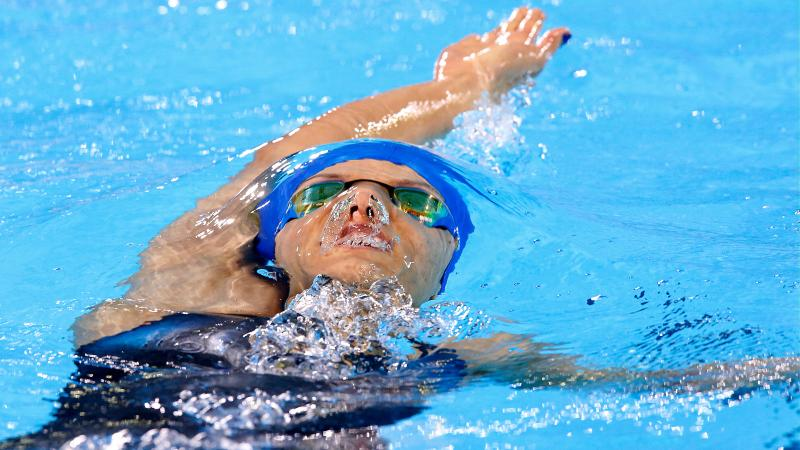 a female Para swimmer doing backstroke