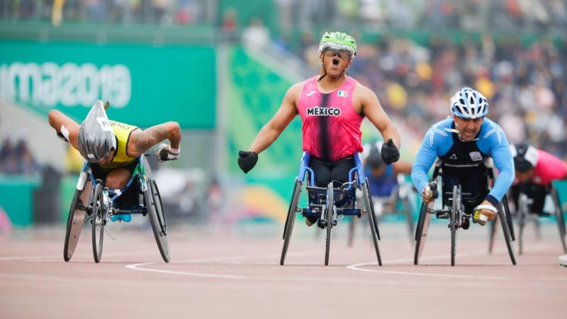 a male wheelchair racer celebrates as he crosses the finish line first