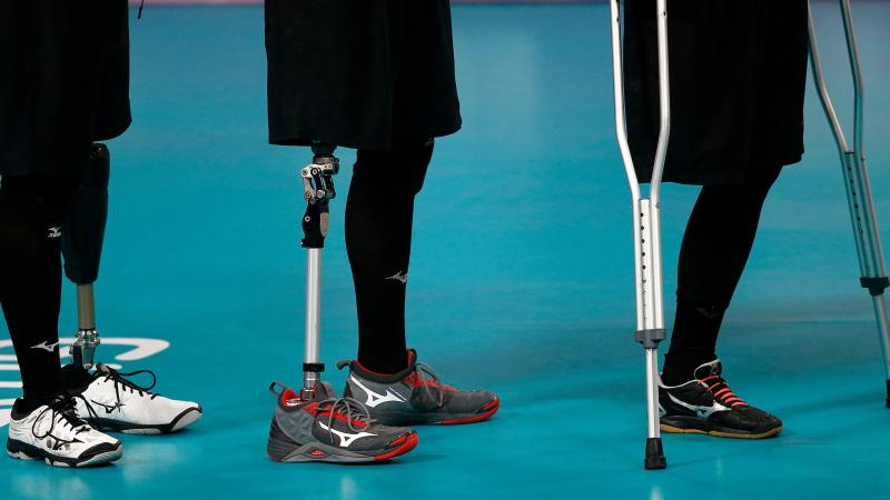 three athletes legs', some with prosthetics