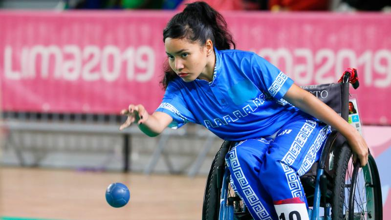 a female boccia player throws a ball