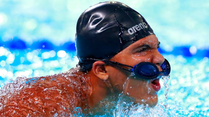 a male Para swimmer in the water with his goggles on his head
