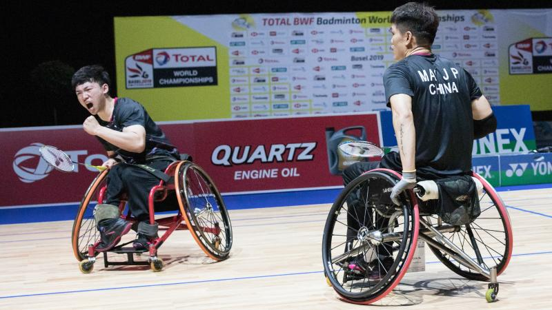 Two male Chinese badminton players in wheelchairs celebrate a point