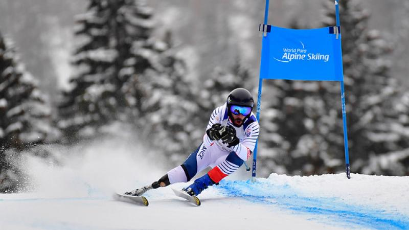 a male Para alpine skier with a prosthetic skiing round a gate