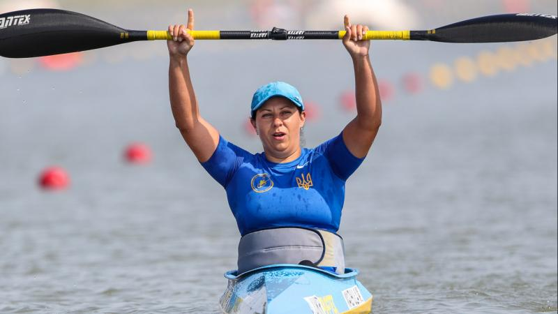 Woman in kayak raises paddle over her head