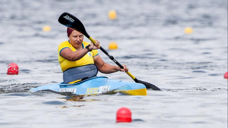 a female Para canoeist mid-stroke on the water