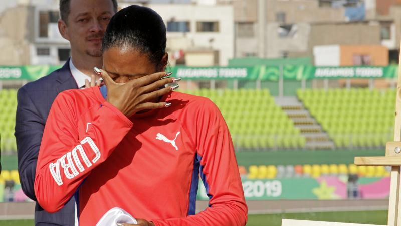 a female Para athlete cries holding her eyes