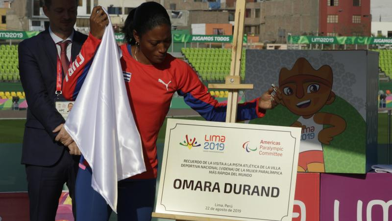 a female Para athlete unveils a plaque with her name on it