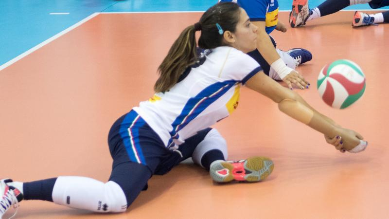 Italian female sitting volleyball player bumps the ball