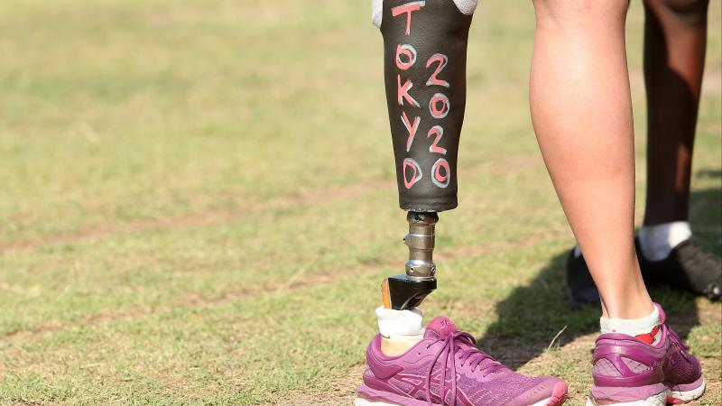 a woman standing with a prosthetic leg that has Tokyo 2020 written on it