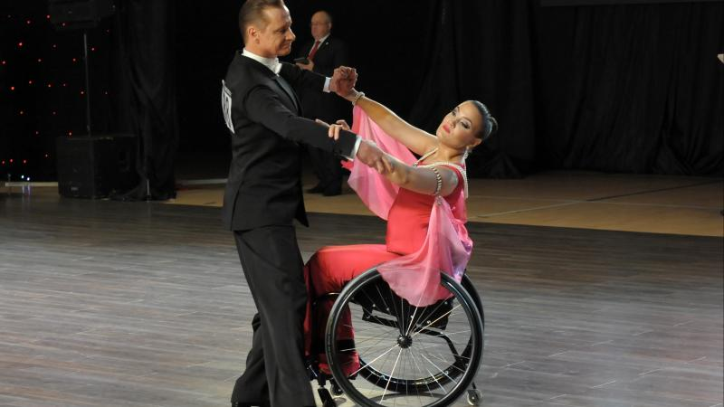 Male standing dancer performs standard dance with female partner in wheelchair
