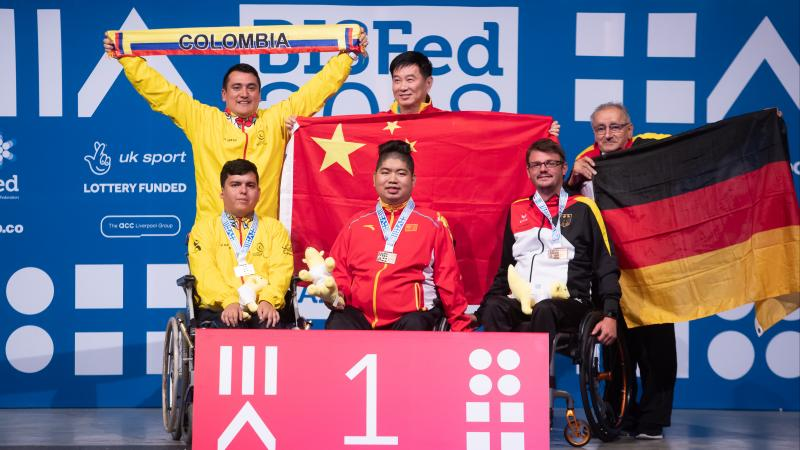 Three boccia athletes and their assistants pose on podium